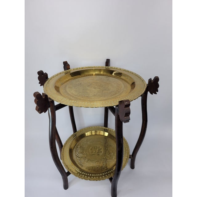 Vintage Asian 2 tier brass tray table with engraved elephants, deer and birds.The wooden frame folding table is very...