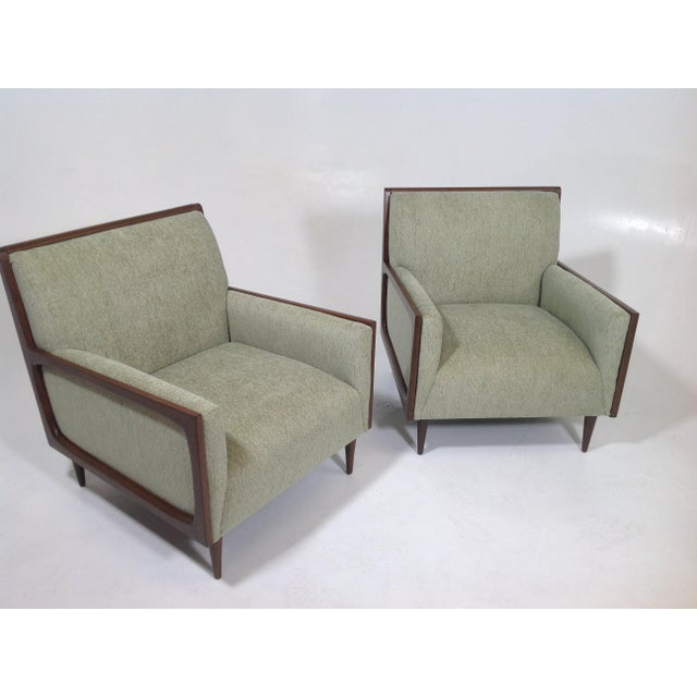 Modern mid-century style lounge chairs. The pair of chairs is newly upholstered and refinished. The chairs are done in a...
