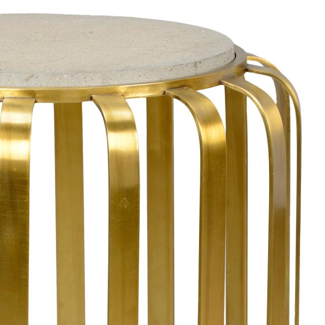 This is the Chelsea House Inc Rogers table. The piece features iron construction, a concrete top, and an antique brass...