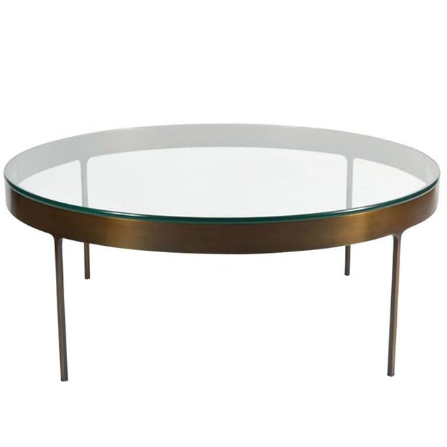 Bronze ring cocktail table with fitted clear glass top. Solid flat bar metal frame with on thin profile legs with interior...