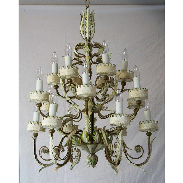 A lovely 18 light Italian tole chandelier. Antiques white paint with green and gold accents. Very sculptural. Lovely...