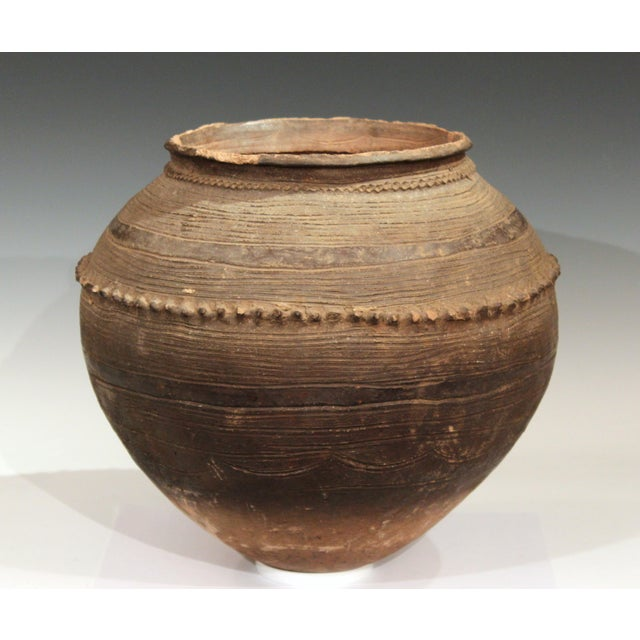 Big old Nigerian coiled terracotta round bottomed storage jar decorated all-over with incised horizontal bands and...