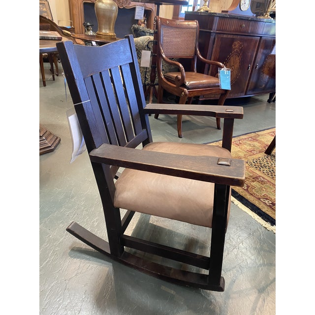 An rare original Gustav Stickley rocking chair with the signature peg design, Stickley back and leather seat that has...