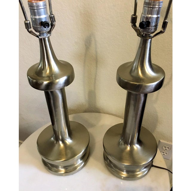 Modernist pair of table lamps in stainless steel by Laurel Lamp Company. Rare style by Laurel will make a great addition...