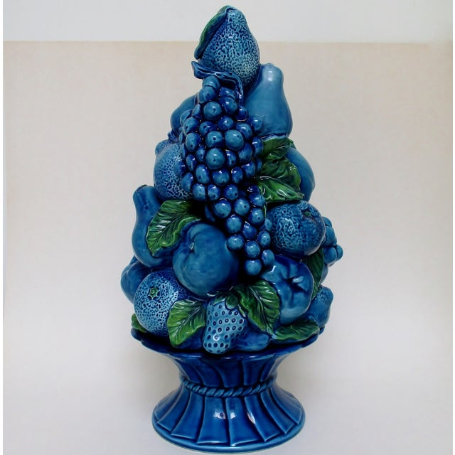 Vintage porcelain fruit topiary in bright blue glaze with green leaves, in the style of Italian accent pieces. The stacked...