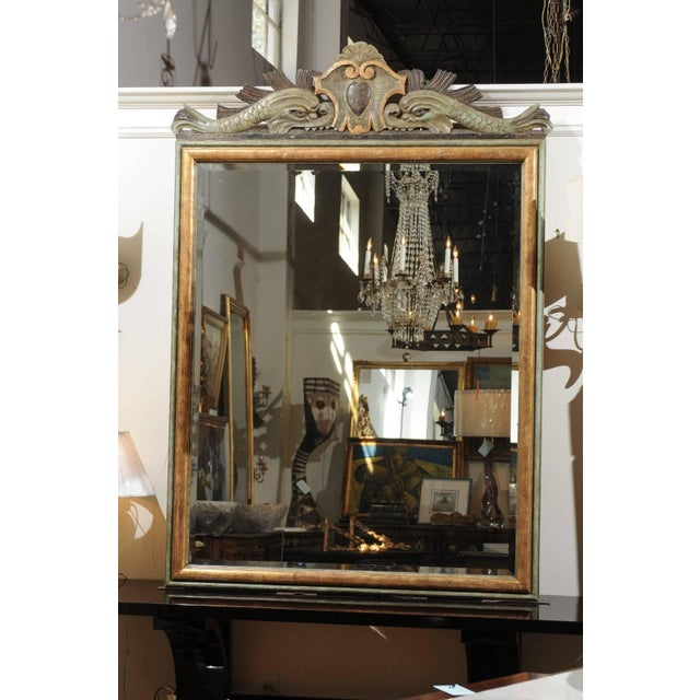 An Italian Baroque style hand-carved painted and gilded rectangular mirror with carved dolphins on the crest. This Italian...