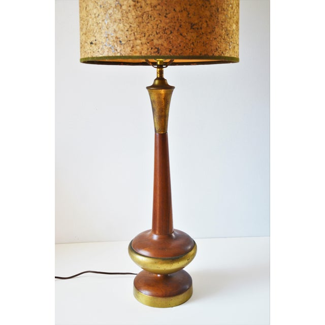 Mid-century walnut and brass table lamp with vintage cork shade. Brass has a nice patina consistent with age and the wood...