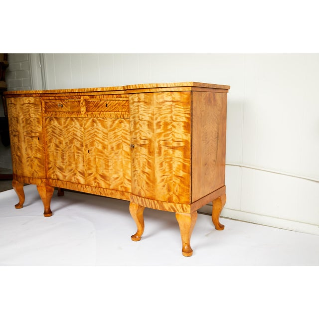 Early 20th century Swedish Art Deco period sideboard/cabinet rendered in highly figured, bookmatched golden flame birch. A...