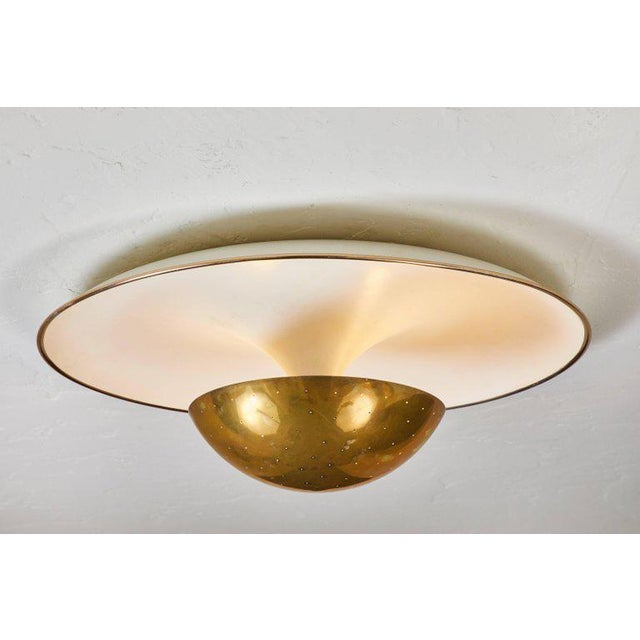 1950s Gino Sarfatti ceiling lamp model #155 for Arteluce. A perforated brass dome on a white painted metal curved plate...
