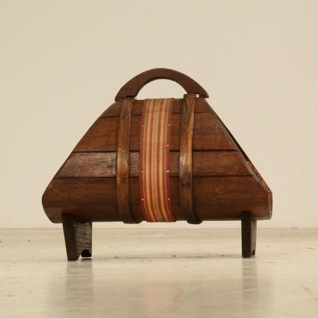 A wooden magazine holder in arts and crafts style with a cloth ribbon around it. Originally used for wine making, now a...