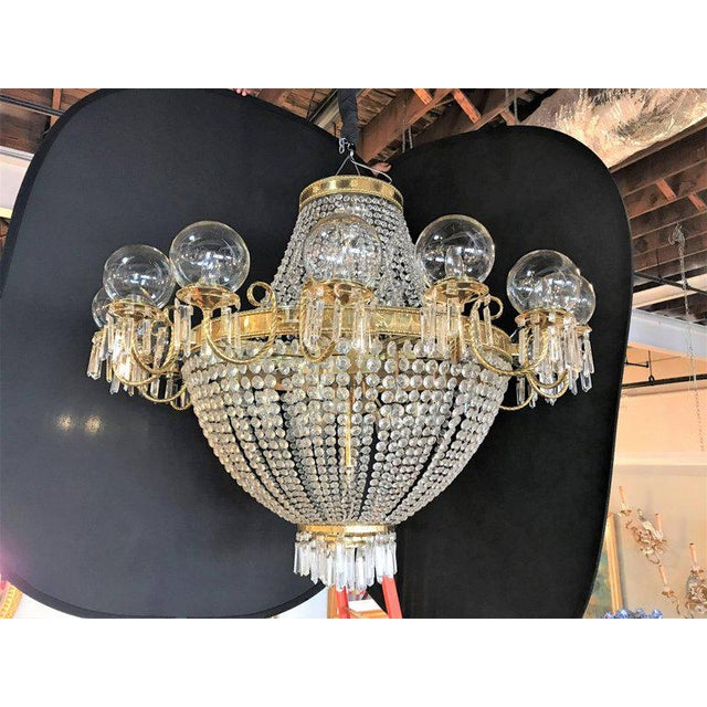 A palatial neoclassical style brass and crystal basket form chandelier with Hanging Prisms. Having 16 globe covered lights...