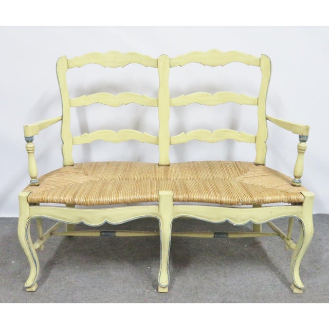 Country French style settee, yellow painted frame with blue highlights, rush seat. Perfect for a rustic home.