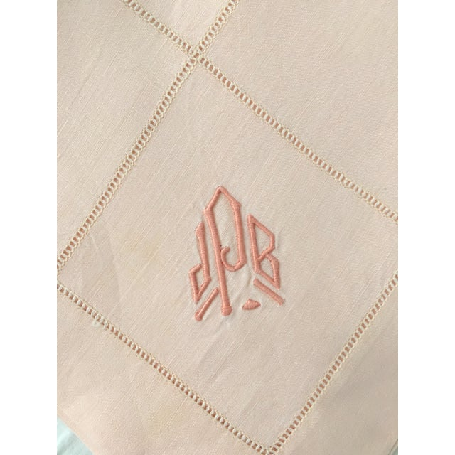 A set of seven vintage ballet pink monogrammed linen dinner napkins, eight matching placemats, and two runners. All...