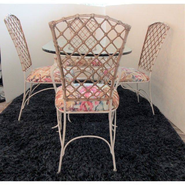 Very unique dining set featuring a thick glass oval table and four chairs. This set has an different combination of iron...