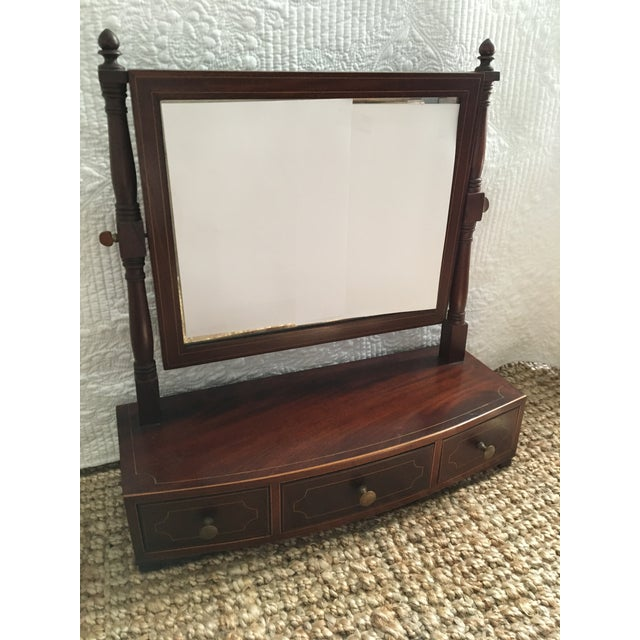 This is an antique mahogany bowfront dressing glass (period term) made in England between 1800-1810 as a lady or...