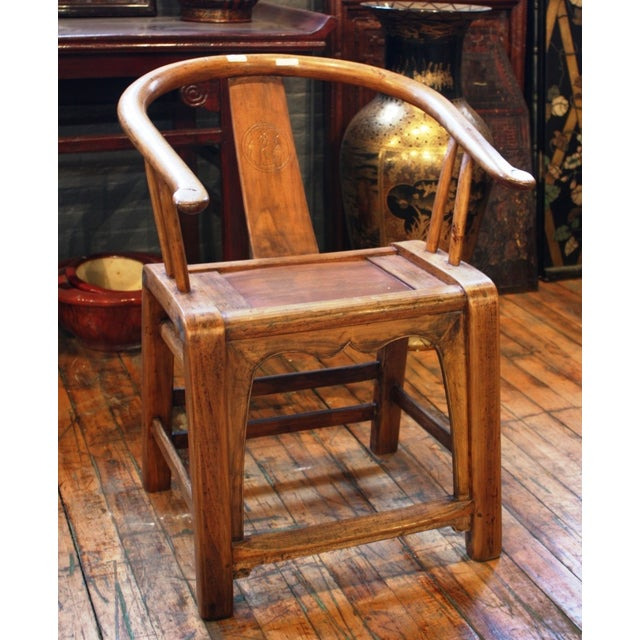This country style small bowback elm armchair features a curved rest, vertical and horizontal supports, and a base...