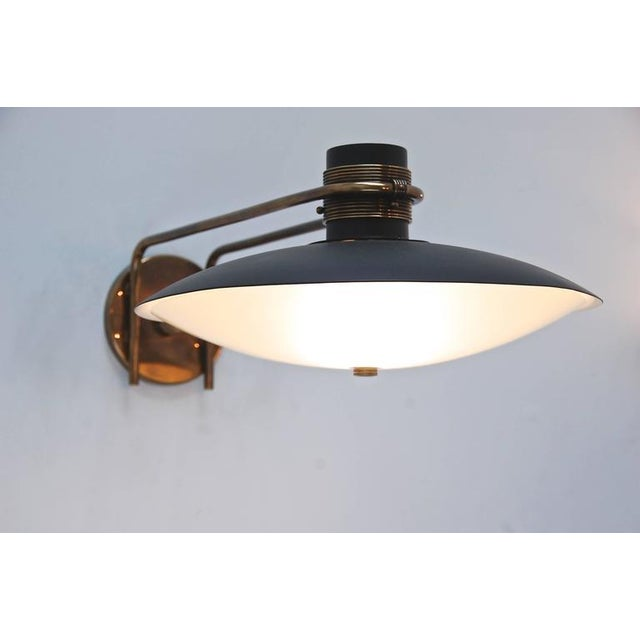 Unique Italian studio wall lamp made from brass, painted aluminum and blown glass. Beautiful hardware frames the dome...