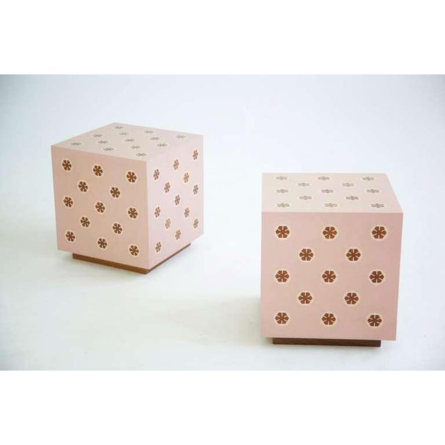 Wormley inspired parquetry end tables on plinth bases. Pale pink poly surface with wooden impressed medallion designs.