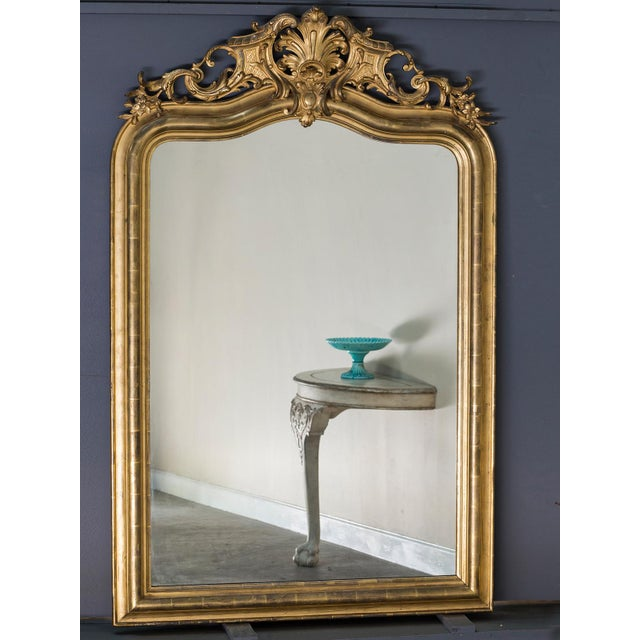 This handsome antique French Louis Philippe gold leaf mirror circa 1890 has a handsome scale and is topped with a...
