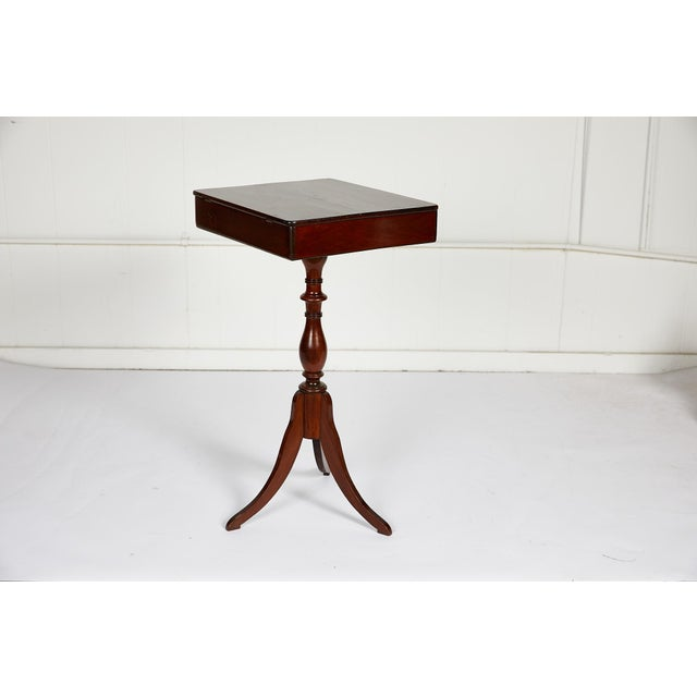 19th century English sewing or side table of mahogany made in the Georgian style. The hinged table top fully opens to...