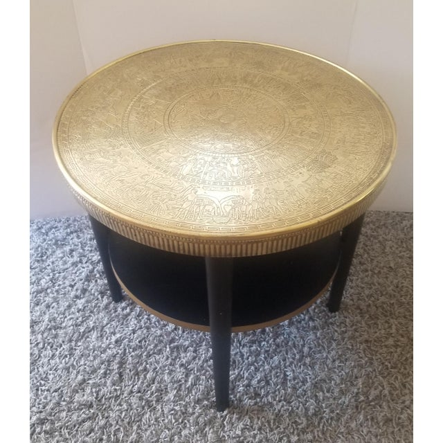 Vintage Egyptian Revival Style Side table. Double tiered table made with solid wood. Top is encased with brass, depicting...