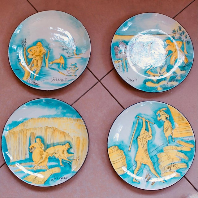 A magnificent set of vibrantly colored Italian faience plates, hand painted with brilliant scenes of traditional everyday...