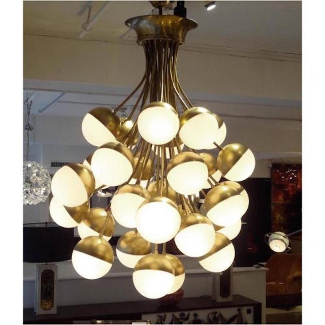 Stilnovo Rare, grand scaled mid century chandelier featuring an inverted bouquet shape in brass with white, opaque glass...