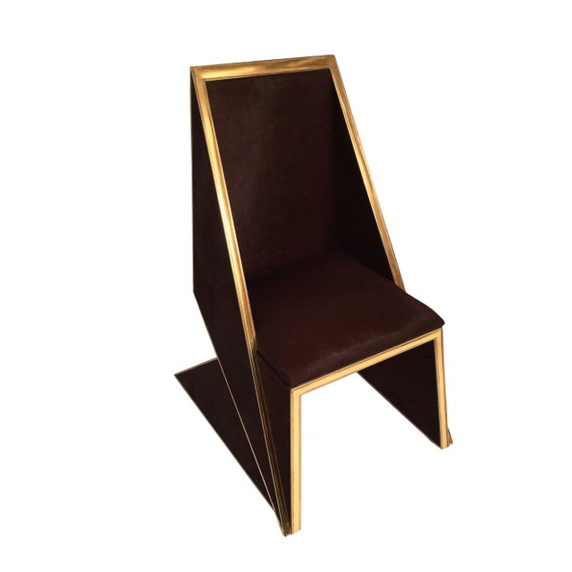 modern triangular two tone chair is made out of solid wood and brown cow hide with accents of 24k gold gilded edges. The...