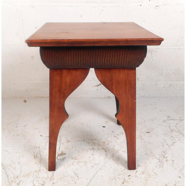 This unique vintage modern table features sculpted legs and a decorative trim underneath the square top. The stylish...