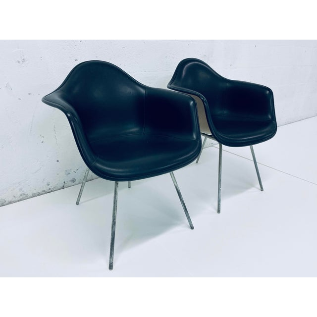 Two black stitched Naugahyde over moulded fiberglass shell DAX chairs by Charles and Ray Eames for Herman Miller. These...
