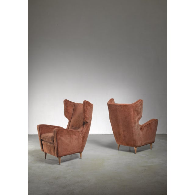 A pair of wingback lounge chairs by Paolo Buffa. The chairs have the original chocolate brown velvet upholstery which is...