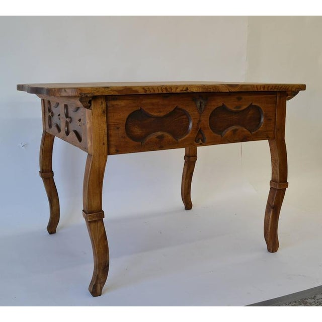 A most unusual find, this substantial pitch pine baroque-style centre table has a thick top, serpentine on all four sides...