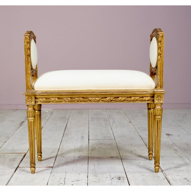 Exquisite, 1920s French Louis XVI-style gilt wood bench with delicately carved decorations throughout. New Belgian linen...