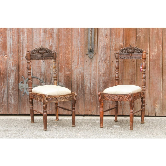 Pair of early 20th Century carved marriage chairs, detailed and hand-carved in teak. Newly upholstered with a vintage...