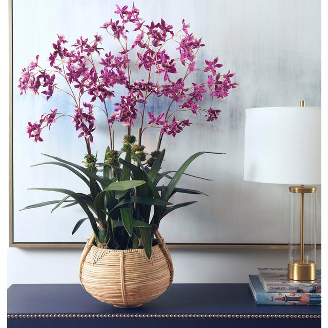 Graceful purple oncidium orchids, planted in a chic cane basket, adds the perfect pop of color. Hand-made to order in our...