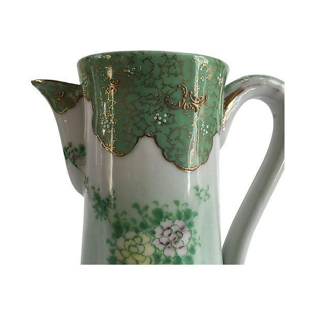 French Art Nouveau porcelain pitcher hand-painted with floral motif and 24K gold accents, featuring a scalloped base....