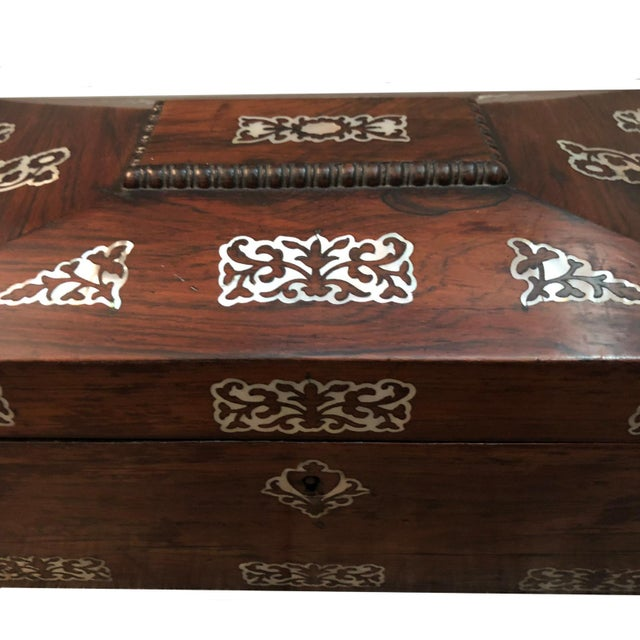 A late classical period English rosewood tea caddy with mother of pearl decoration. The caddy has two covered tea wells...