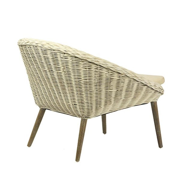 """White distressed rattan chair with a linen blend off-white loose cushion and grey wash wooden legs. The seat height is 16""""."""