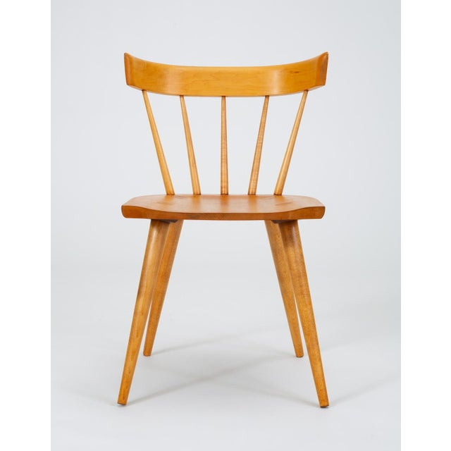 A set of four dining chairs in solid maple from Paul McCobb's iconic Planner Group, manufactured from 1950-1964 by...