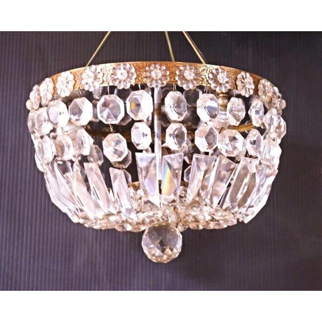 Express a distinct style and taste with this striking yet elegant dome form chandelier with brass frame and crystal...