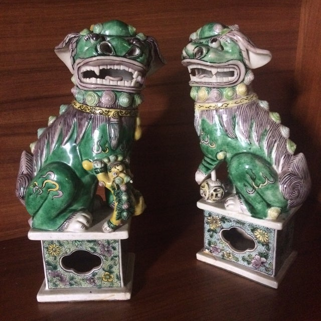 """Exquisite hand painting and sculptural detail, this pair of """"famille-verte"""" porcelain biscuit figures of Buddhist..."""
