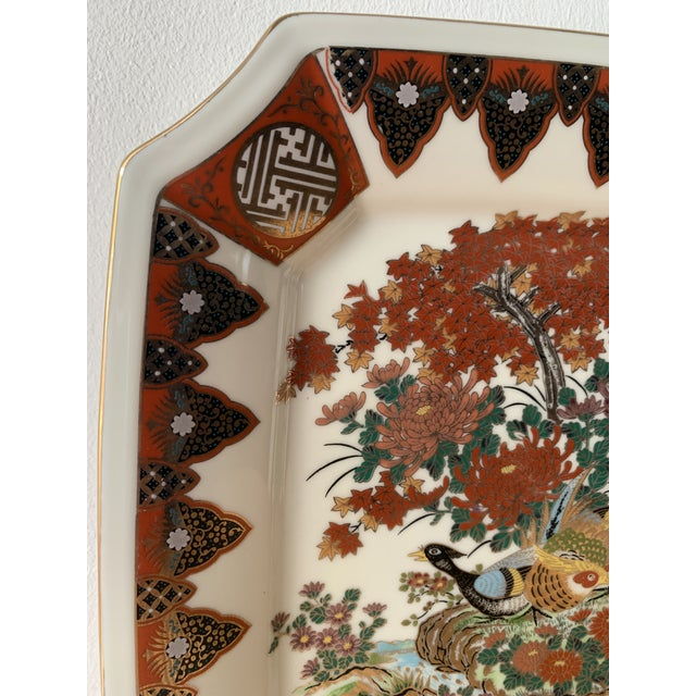 Large porcelain plate with peacocks and chrysanthemums. Painted with detailed japanese symbols and shapes. Orange, red,...