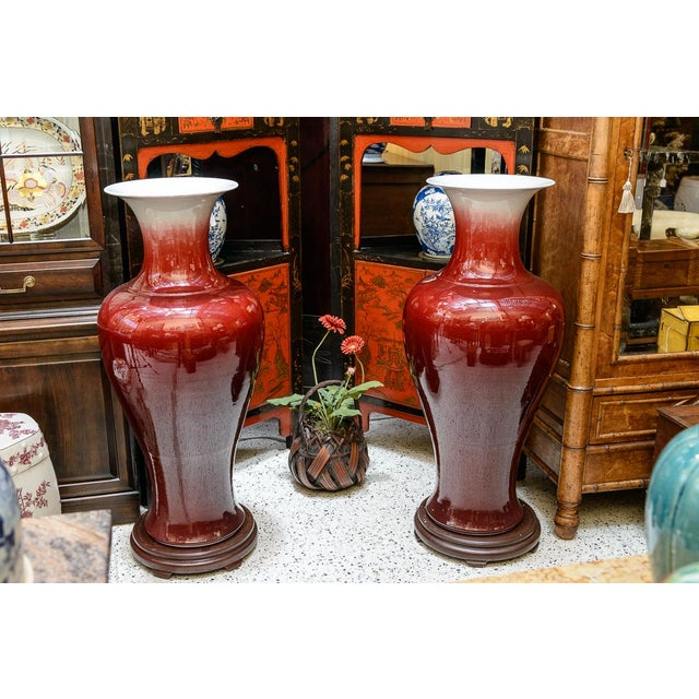 Pair of large oxblood floor vases. Stands included.