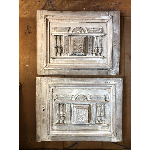 Pair of stripped and bleached antique French paneled architectural cabinet doors with carved elements of columns, arched...