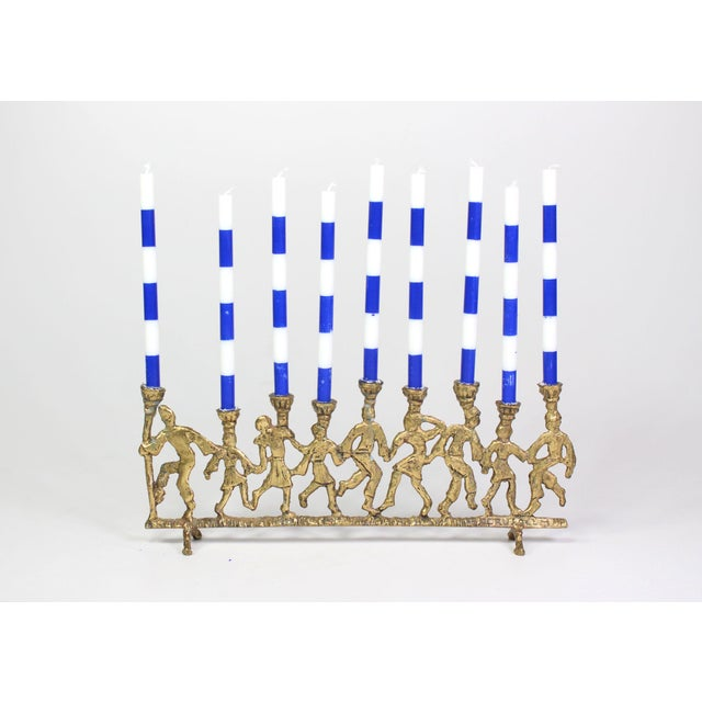 Featured is a vintage mid-century brass Menorah from the 1950's - 1960's depicting festive celebratory dancing folk....