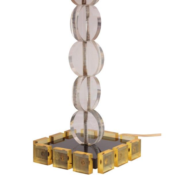 This mid-century lucite table lamp has unique details. The clear lucite discs make the stem of the lamp. Pale lemon lucite...