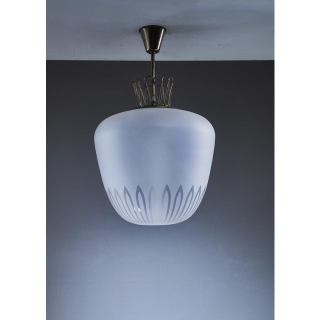 A large, elegant Swedish pendant lamp from the 1940s. The lamp is made of a frosted glass diffuser with a geometric...