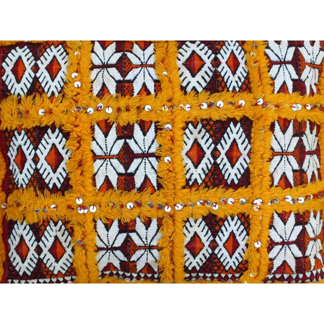 Handwoven Moroccan Berber pillow sham with an elaborate diamond pattern and an ornate orange sequined grid. Striped back....