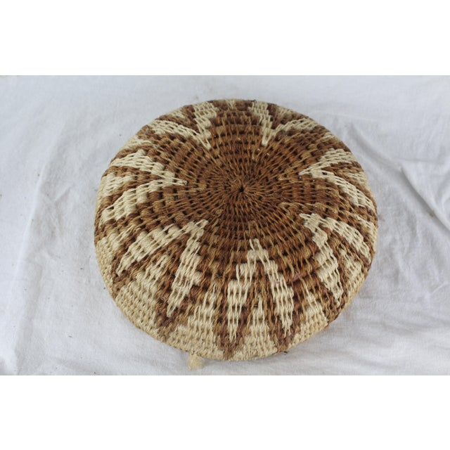 Handwoven grass African tribal basket in starburst pattern with varying shades of brown and tan.