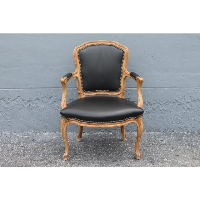 This is a beautiful mid-century Louis XV style carved walnut armchair. The piece is upholstered in a beautiful black textile.
